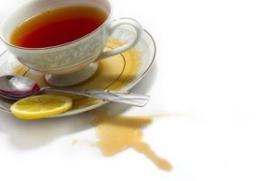 cup_of_tea_with_spill_on_table_cloth_l